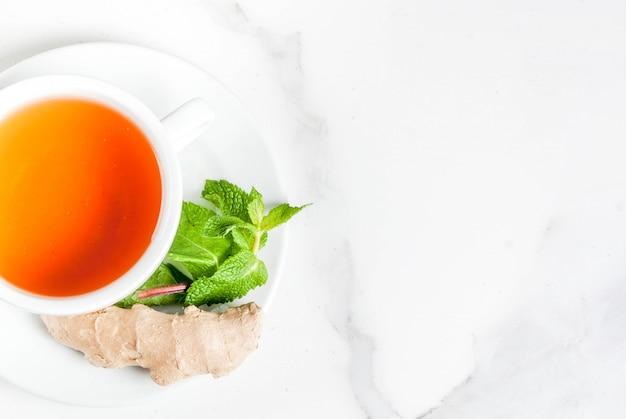 Xícara de chá de gengibre com limão, hortelã fresca e mel