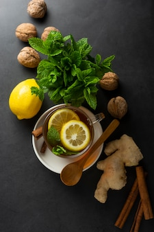 Xícara de chá de gengibre com limões e folhas de hortelã na superfície escura,