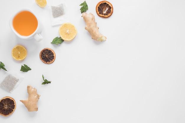 Xícara de chá de gengibre; fatia de limão; toranja seca; ervas e saquinhos de chá em pano de fundo branco