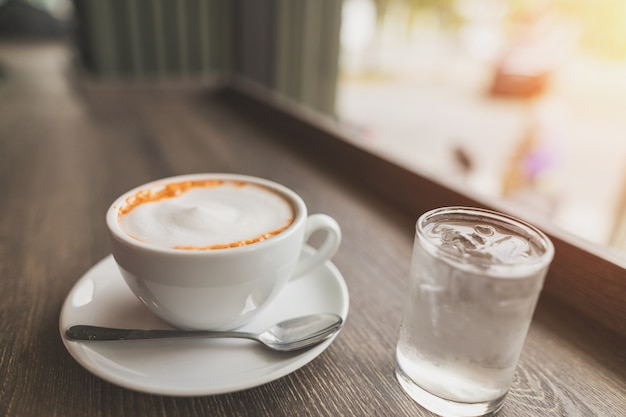 Xícara de chá de leite em uma mesa de madeira