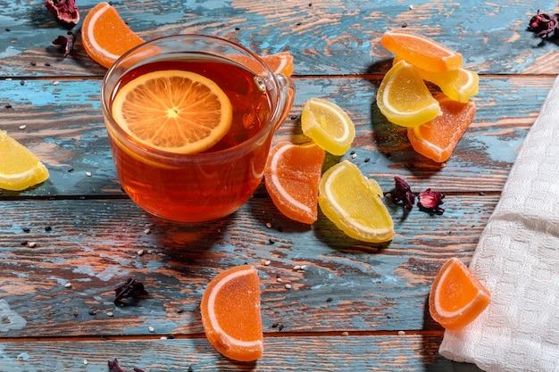 Xícara de chá de limão e fatias de geleia de limão e laranja em uma mesa rústica de madeira