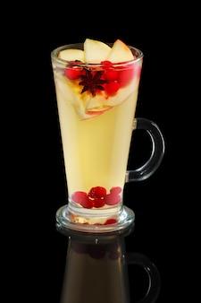 Xícara de chá de maçã com cranberry e canela isolado no preto