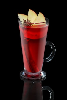 Xícara de chá de maçã e cereja com pau de canela isolado na balck