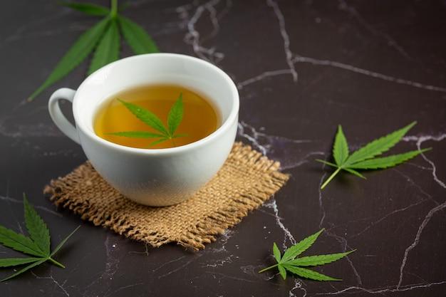 Xícara de chá de maconha com folhas de maconha colocada no chão de mármore preto