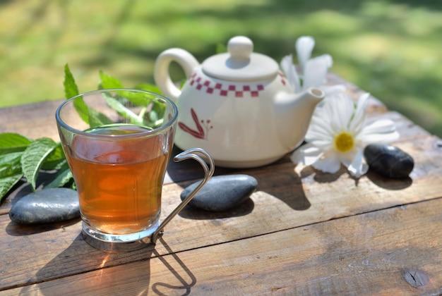 Xícara de chá de menta e bule em uma mesa de madeira no jardim entre folhas frescas e flores brancas