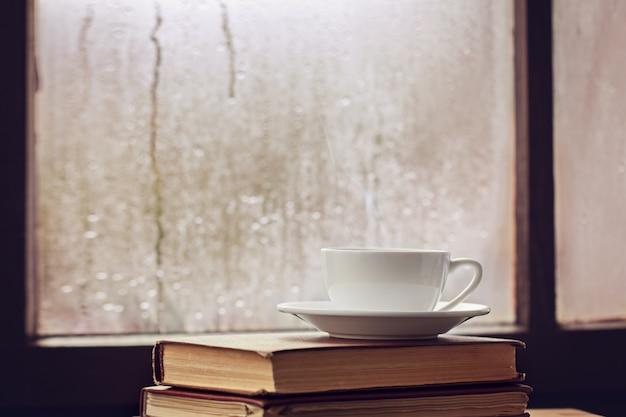Xícara de chá de outono ou coffeeon janela chuvosa