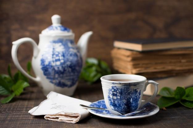 Xícara de chá de porcelana antiga e bule com livros e guardanapo dobrado na mesa de madeira