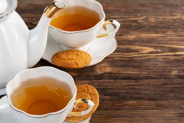 Xícara de chá de porcelana branca e biscoitos de aveia em uma mesa