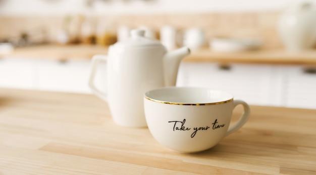 Xícara de chá de porcelana branca e bule de chá da tarde em uma mesa de cozinha branca em uma mesa de madeira
