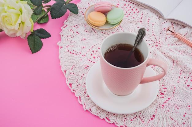 Xícara de chá-de-rosa com macaroons na toalha de mesa de renda contra fundo rosa