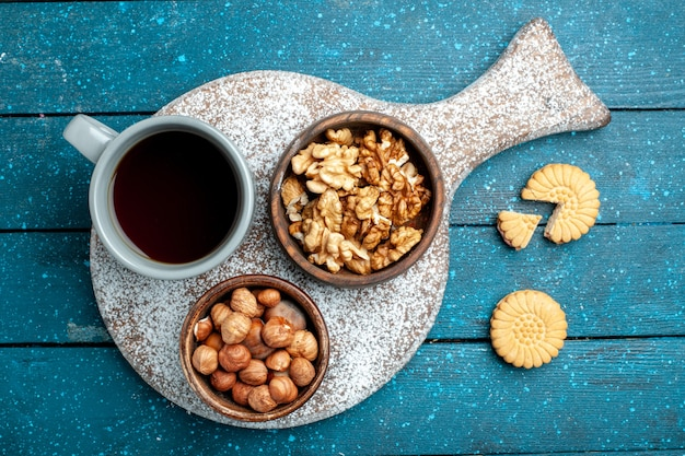 Xícara de chá de topo com nozes e avelãs na cor azul rústica mesa porca lanche chá