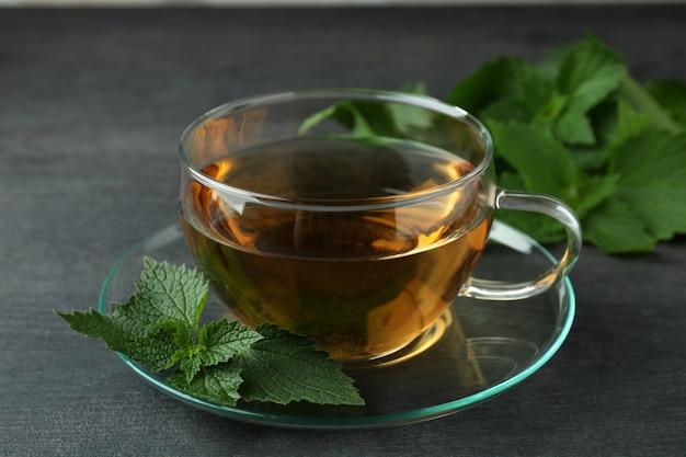 Xícara de chá de urtiga na mesa de madeira escura