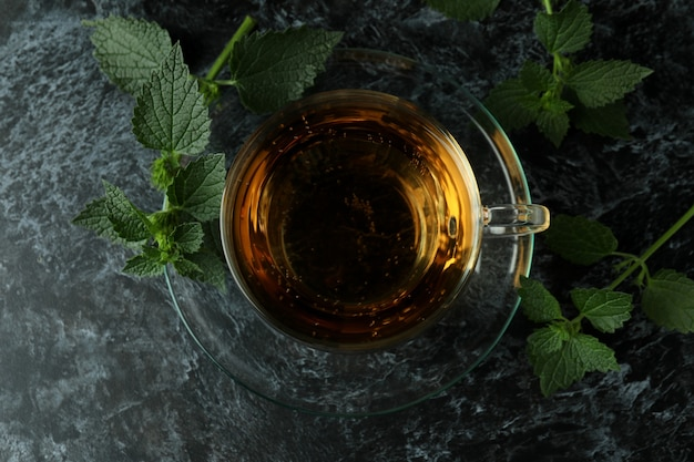 Xícara de chá de urtiga na mesa esfumada preta