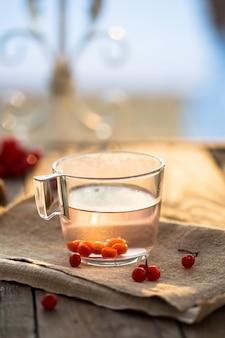 Xícara de chá de viburno e tomilho em uma mesa de madeira. chá de vitaminas para resfriados.