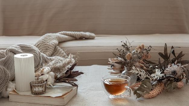 Xícara de chá de vidro, elemento de malha e flores secas no interior da sala