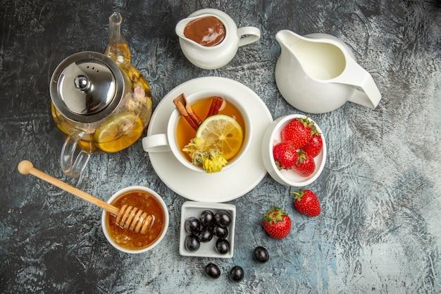 Xícara de chá de vista de cima com azeitonas mel e frutas em comida de café da manhã de superfície escura