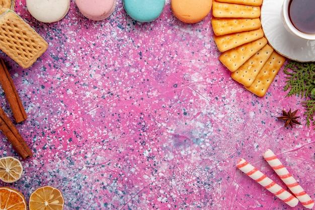 Xícara de chá de vista de cima com biscoitos e macarons franceses na mesa rosa