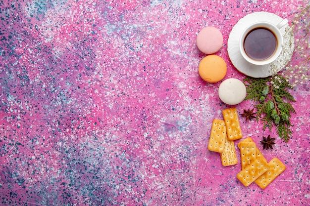 Xícara de chá de vista de cima com biscoitos e macarons franceses na superfície rosa