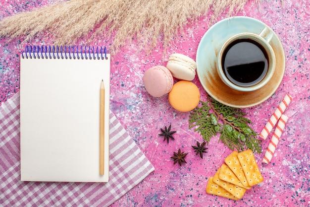 Xícara de chá de vista de cima com bloco de notas de biscoitos e macarons na superfície rosa