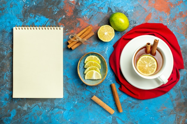 Xícara de chá de vista de cima com bloco de notas xale vermelho de limão e canela na superfície azul vermelha