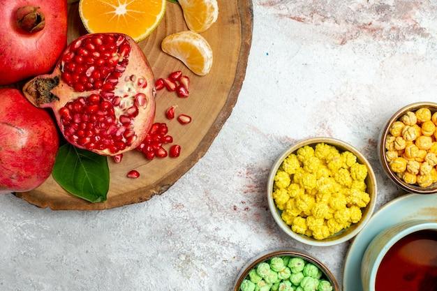 Xícara de chá de vista de cima com bombons e frutas no espaço em branco