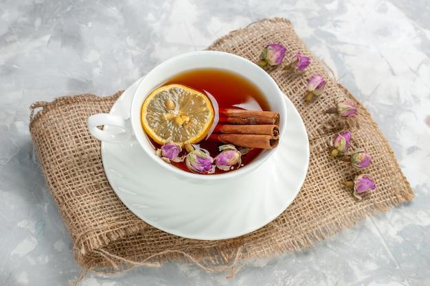 Xícara de chá de vista de cima com canela e limão na superfície branca