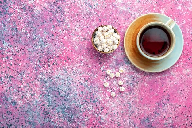 Xícara de chá de vista de cima com confitures doces brancos na superfície rosa