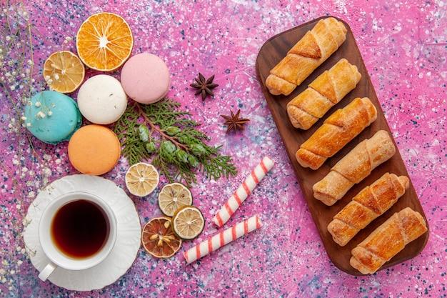 Xícara de chá de vista de cima com macarons franceses coloridos e bagels na parede rosa biscoito bolo de açúcar torta doce de chá biscoito