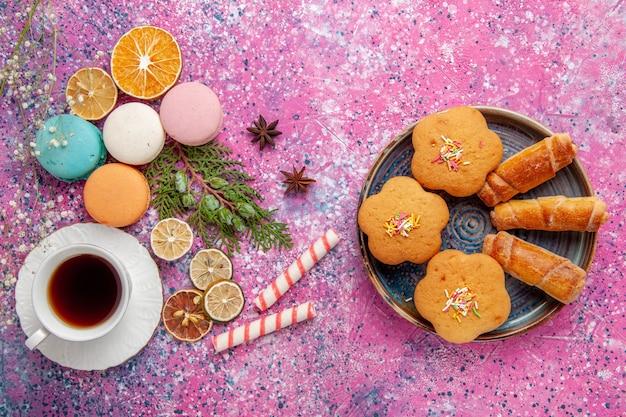 Xícara de chá de vista de cima com macarons franceses coloridos e bagels na parede rosa biscoito bolo de açúcar torta doce