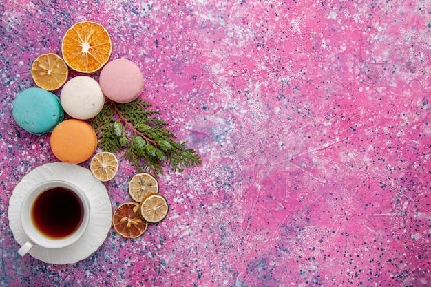 Xícara de chá de vista de cima com macarons franceses coloridos e waffles no chão rosa bolo biscoito açúcar torta doce chá