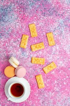 Xícara de chá de vista de cima com macarons franceses e biscoitos na mesa rosa