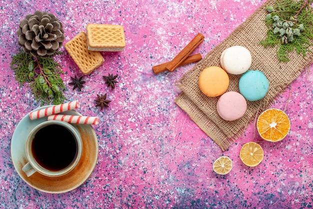 Xícara de chá de vista de cima com macarons franceses na mesa rosa