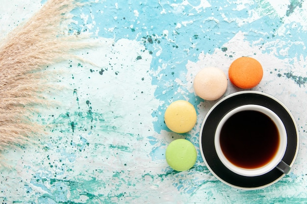 Xícara de chá de vista de cima com macarons franceses na superfície azul clara