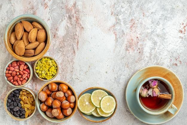 Xícara de chá de vista de cima com passas, nozes e rodelas de limão na superfície branca de frutas chá cítrico bebida