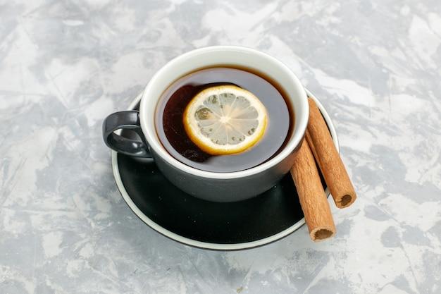 Xícara de chá de vista de cima dentro da xícara e prato com canela na superfície branca