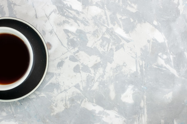 Xícara de chá de vista de cima dentro da xícara e prato na mesa branca