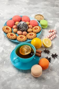 Xícara de chá de vista frontal com biscoitos de macarons franceses e bolos na superfície branca biscoitos de açúcar e bolos doces biscoitos
