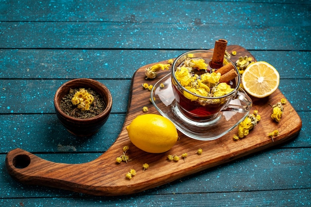 Xícara de chá de vista frontal com canela e limão na mesa azul