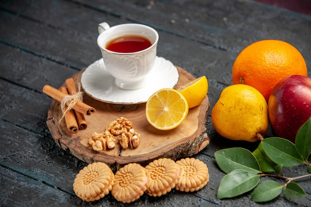 Xícara de chá de vista frontal com frutas e biscoitos no chão escuro