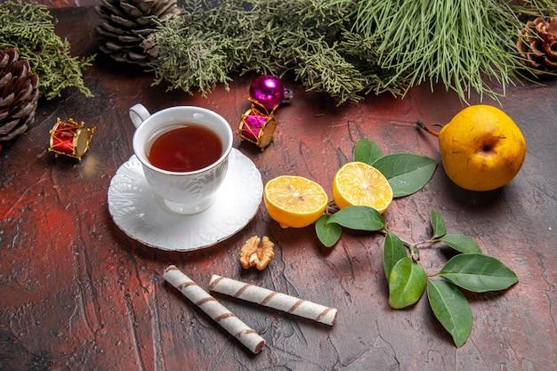 Xícara de chá de vista frontal com limão e árvore em fundo escuro