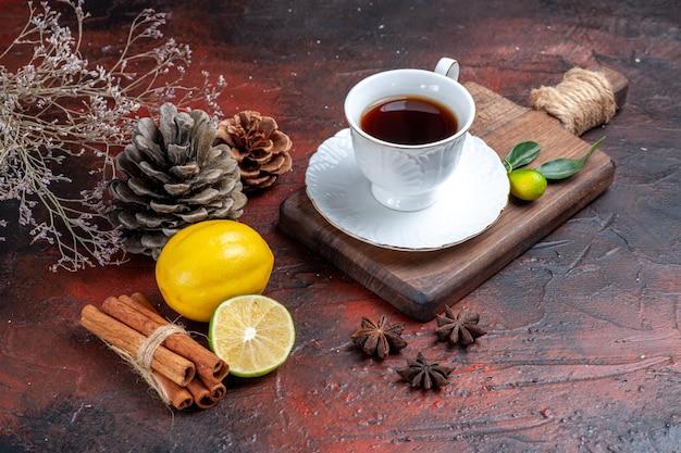 Xícara de chá de vista frontal com limão e canela no fundo escuro