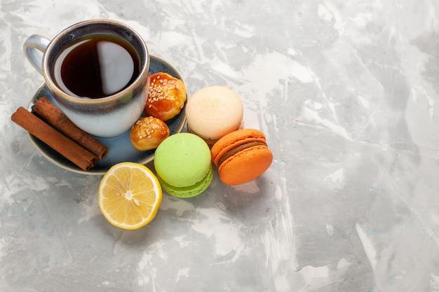 Xícara de chá de vista frontal com macarons de canela e bolinhos na parede branca biscoito bolo doce biscoito torta de açúcar
