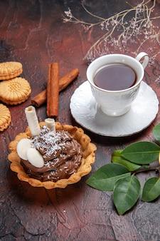 Xícara de chá de vista frontal com um delicioso pequeno bolo em fundo escuro