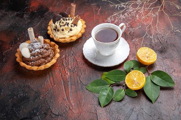Xícara de chá de vista frontal com um pequeno bolo em fundo escuro