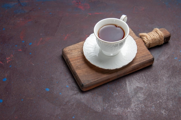 Xícara de chá de vista frontal dentro de copo de vidro com prato no espaço escuro