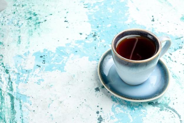 Xícara de chá de vista frontal na superfície azul