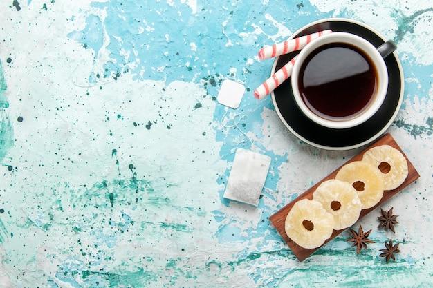 Xícara de chá de vista superior com anéis de abacaxi secos na superfície azul