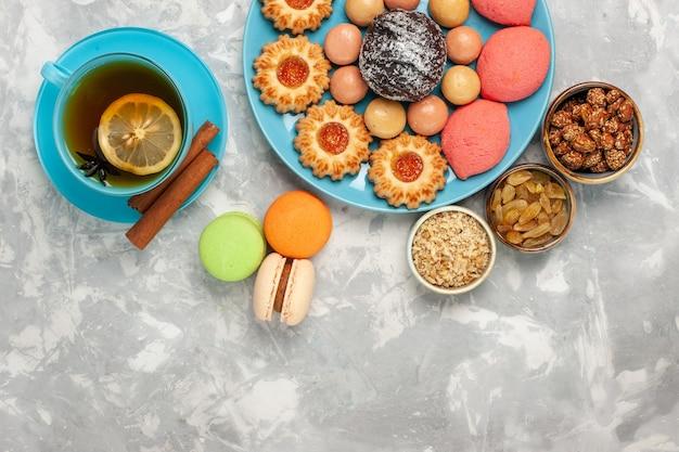 Xícara de chá de vista superior com biscoitos e bolos de macarons franceses na superfície branca