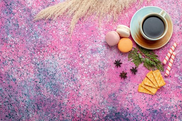 Xícara de chá de vista superior com biscoitos e macarons em uma superfície rosa claro
