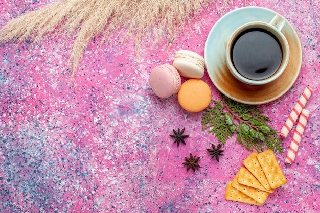Xícara de chá de vista superior com biscoitos e macarons na superfície rosa